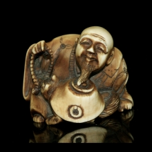 Japanese ivory Netsuke carving of an old man playing with a fox, Edo