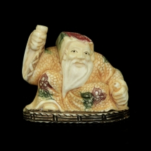 Japanese painted ivory Netsuke carving of an old bearded man holding a bottle of sake