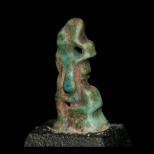 A New Kingdom blue-green faience amulet of a seated Pharaoh