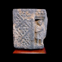 A Gandharan grey schist stupa fragment showing a worshipper within a recess beside a decorative panel.