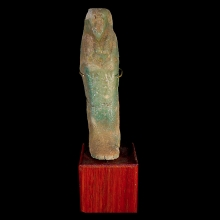 A turquoise-glazed faience ushabti, featuring some hieroglyphic text on front panel