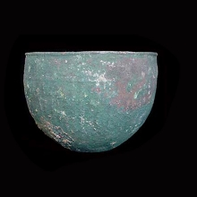 A Western Asiatic bronze vessel of deep form and decorated with ribbing.