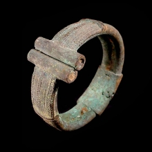 An archaic Dogon bronze bracelet with feathered and braided designs.