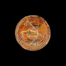 An attractive Persian glazed ceramic dish, the interior decorated with a design of three fish.