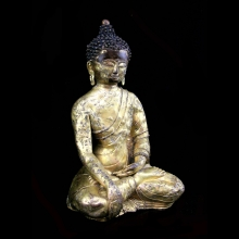 A fine and early Tibetan gilt bronze cast seated Buddha, 14th Century.