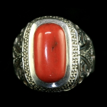 A silver ring with natural red coral bezel