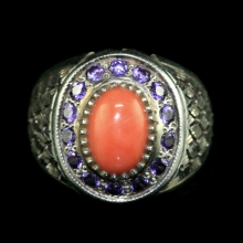A silver ring with natural red coral bezel and amethyst frieze