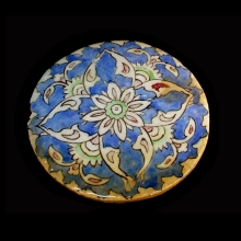 Islamic round glazed pottery tile with floral motif