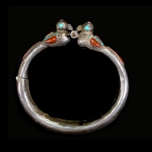 Persian tribal silver bracelet with blue glass and carnelian inlay; terminals in bird form.