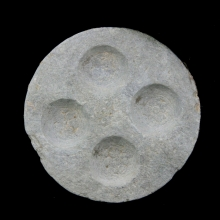 A Gandharan cosmetic palette of silvery-grey schist, the four recesses decorated with carved rosette designs.