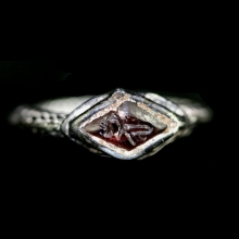 Indian silver ring with garnet bezel engraved with symbol of Vishnu.