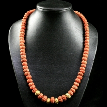 A necklace comprising natural red carved coral beads in melon form with modern gold elements, Mughal 17th Century
