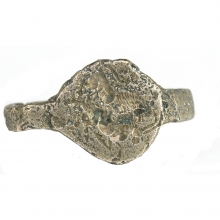 A Sassanian votive silver alloy ring, the bezel depicting a lion attacking an ibex.