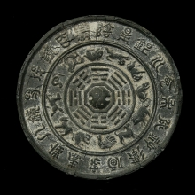 A Ming Dynasty lead and tin mirror shaped charm the front surface with the horoscope.