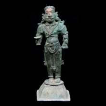 An Indian brass statuette of a dignitary holding implements