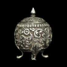 An Indian silver pepper pot with floral motif