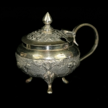 An Indian silver salt or mustard pot with a lion fox and tiger in relief