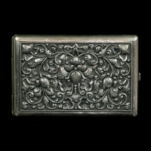 A Cambodian silver cigarette case embossed with floral motif.