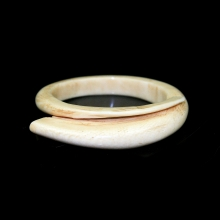 A pre-ban ivory bangle carved to resemble a circular pigs tusk