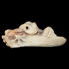 An Eskimo Inuit fossil walrus ivory carving depicting a tree frog on a branch.