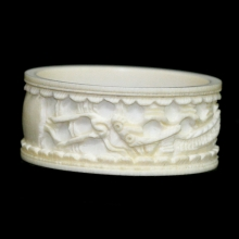 A Qing to Republic carved ivory napkin ring with dragon motif.
