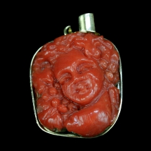 A carved Sardinian natural red coral figurative pendant set in 18 carat gold