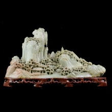 A Chinese soapstone carving depicting a village nestled on a rocky mountain.