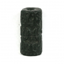 A Bactrian black steatite cylinder seal engraved with a pair of warriors amongst wild beasts.