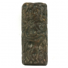 A Bactrian brown haematite cylinder seal engraved with a pair of warriors holding an eagle below an ibex and swastika symbols in the field
