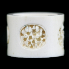 A Qing to Republic carved ivory napkin ring four shallow recessed village scenes.