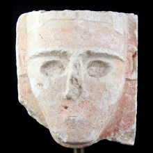 A Sabean limestone stele with a face in high relief.