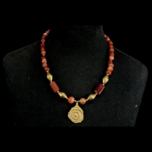 An ancient Anatolian necklace comprising carnelian beads and foil gold central pendant interspersed with 19th to 20th Century gold beads